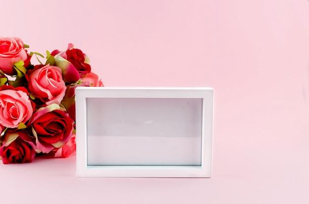 Подарочная коробка, розы и пустая рамка на розовом фоне