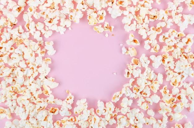 ピンクのパステル調の背景に散らばってポップコーン
