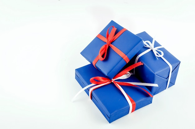 Красные, синие и белые подарочные коробки с лентами на белом фоне