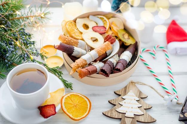 木製のテーブルにドライフルーツチップと紅茶とギフトボックス