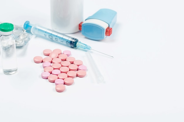 Таблетки, шприц, перчатки на белом столе