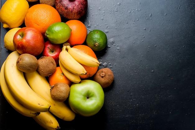 黒の背景に多くの様々な果物