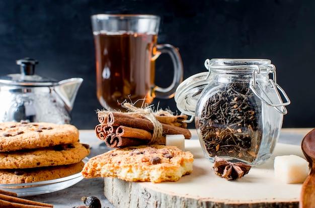 お茶、自家製クッキー、暗い背景にお茶のスパイスの瓶、