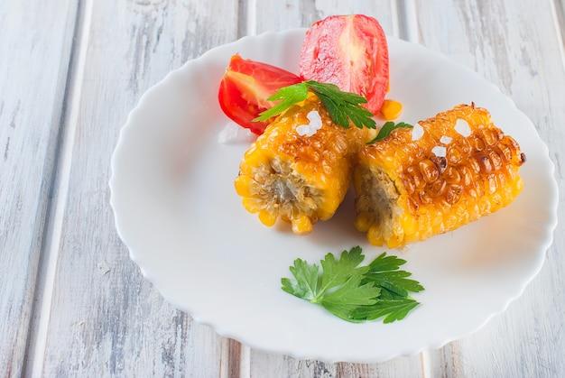 皿にトマトと野菜のグリル焼きトウモロコシ