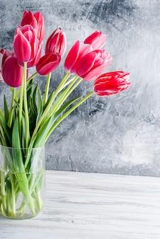 灰色の背景上のガラス花瓶にピンクのチューリップの花束。