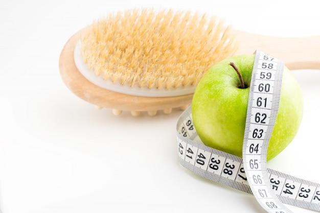 巻尺と白い机の上の単一の青リンゴとドライマッサージブラシ。健康とダイエット