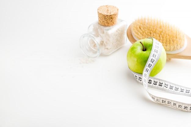 巻尺の乾式マッサージブラシ。白い机の上の海の塩と単一の青リンゴとガラス瓶。健康とダイエット