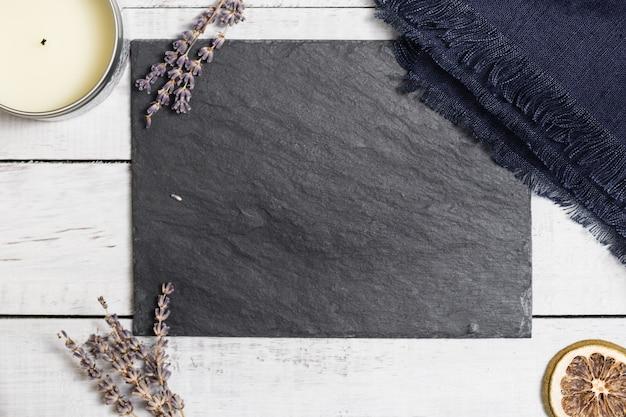 白い素朴な木製のテーブルの上の黒いグラファイトボード上のラベンダー。