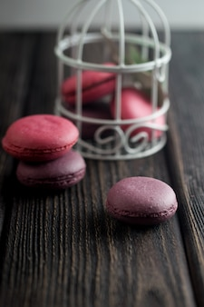 イチゴ、クリーム、チョコレート、ブルーベリーのマカロンのグループ。素朴な写真。