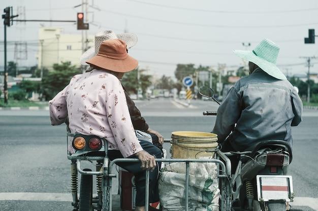アジアの家族が赤信号で駐車してバイクを変更します