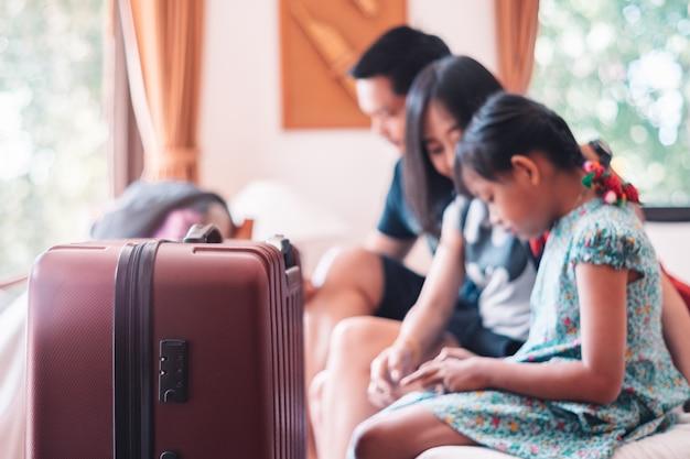 バックグラウンドでベッドの上に座って幸せなアジア家族とホテルの部屋の床に立っている大きな車輪付きスーツケース