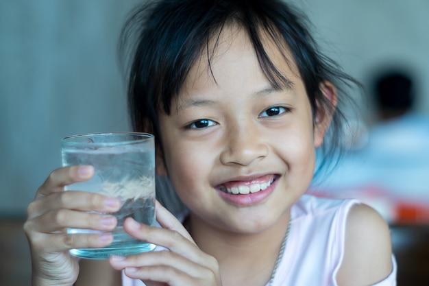笑顔のアジアの子供の女の子は、氷の水のガラスを保持します