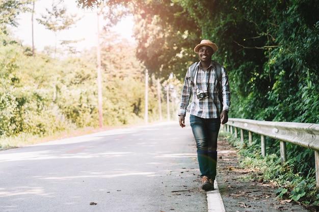 Африканский человек путешествия рюкзак, идущий по дороге шоссе