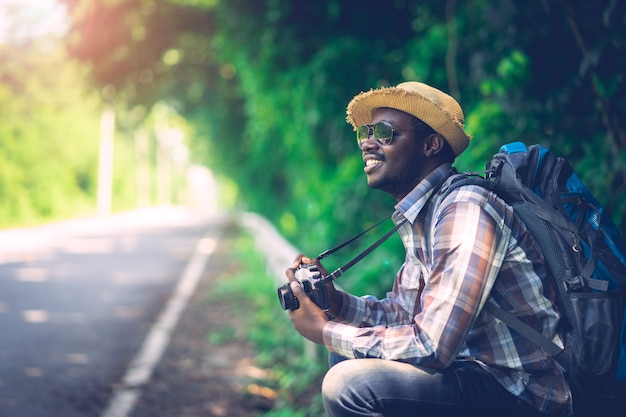 Африканский человек путешественник, несущий рюкзак и держащий камеру стороной шоссе