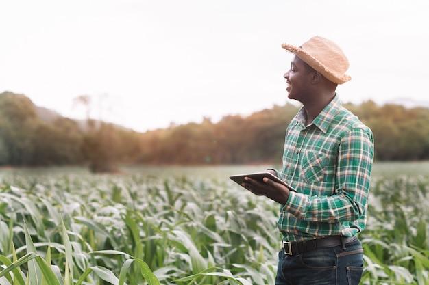 アフリカの農家は、タブレットを保持している緑の農場に立つ