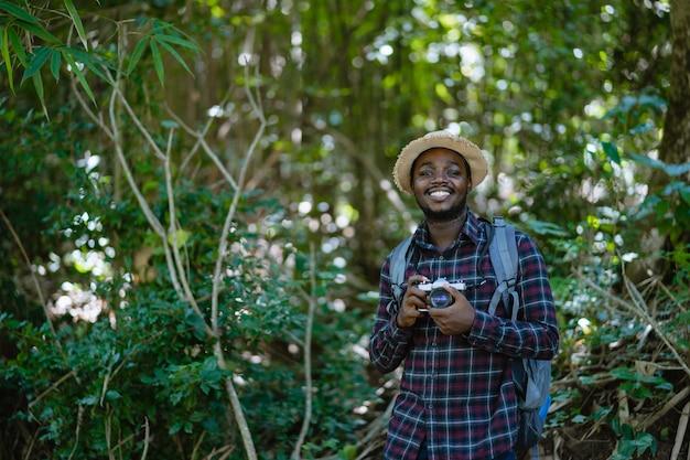 Африканский путешественник человека свободы держа камеру при рюкзак стоя в зеленом естественном лесе.