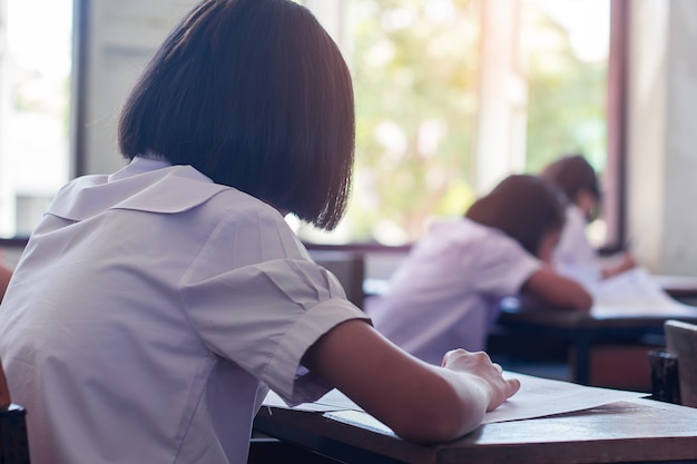 Студенты сдают экзамен со стрессом в школьном классе.