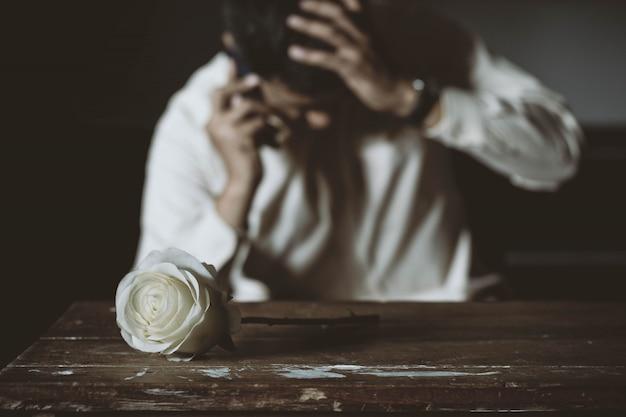 スマートフォンを話している深刻な男とテーブルの上のバラ。低キースタイル。