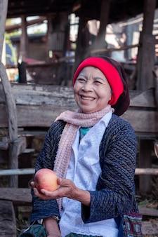 Азиатская старшая женщина держа и есть яблоко с большой улыбкой