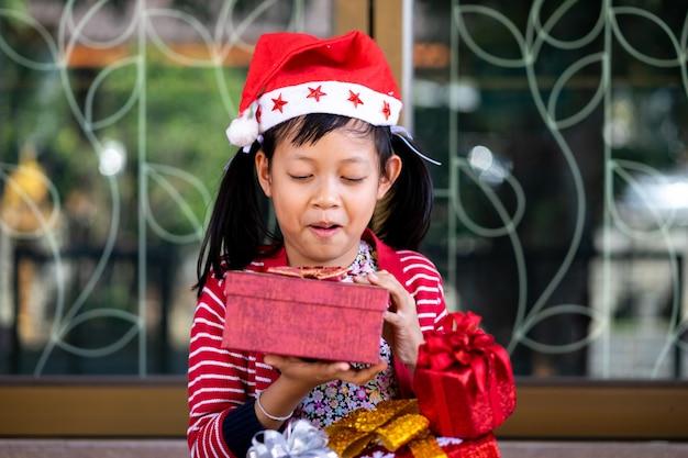 アジアのかわいい女の子が興奮してホリデーギフトを受け取る