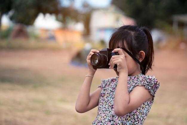 フィルムカメラを押しながら写真を撮るアジアの小さな子供の女の子