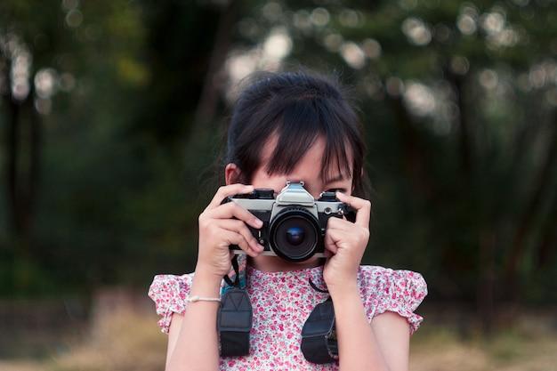 Портрет азиатской жизнерадостной маленькой девочки принимая фото с камерой фильма