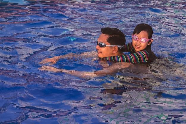 父と娘が一緒に泳ぐ