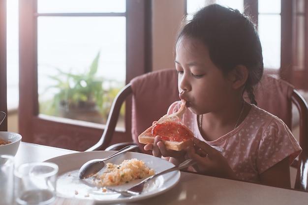 Азиатская девушка ребенка есть хлеб и варенье в завтрак