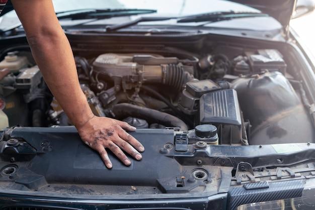 Автомеханик ищет и анализирует до ремонта двигателя в гараже