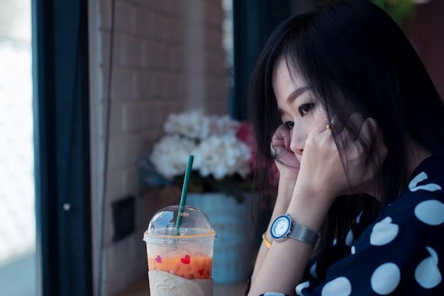 Азиатская грустная женщина возле окна, думая о чем-то с одиночеством