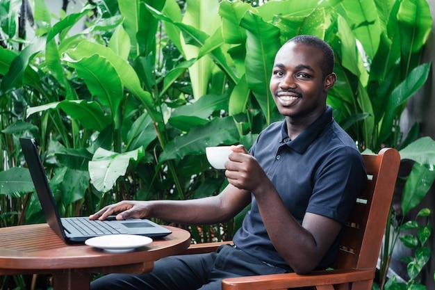 Человек, используя портативный компьютер за пределами кафе