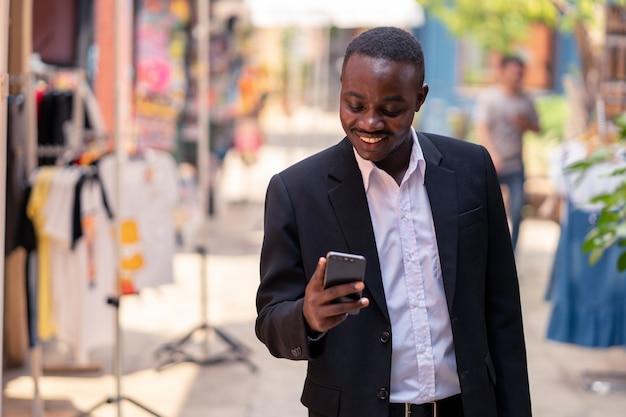 Африканский деловой человек, используя свой телефон и прогулки по городу