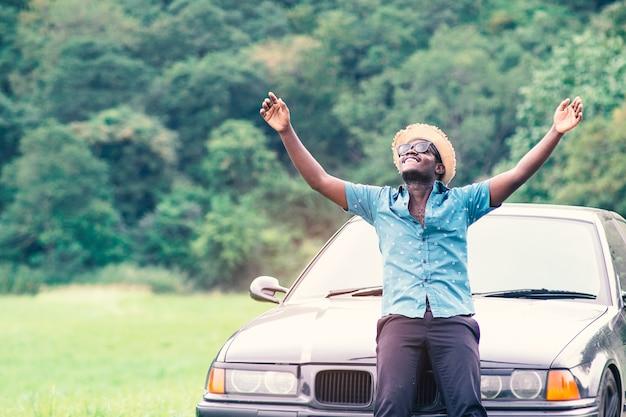 アフリカの旅行者は幸せに車のスカートに座っています。