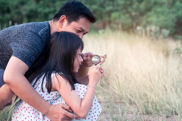 幸せなアジア家族の父と娘が虫眼鏡で自然を探索します。