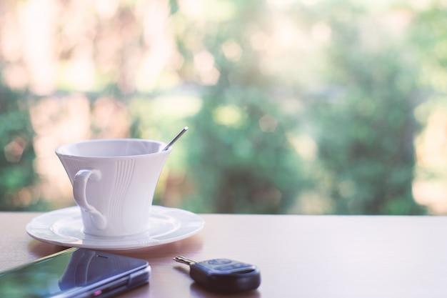 Горячий кофе с ключом и смартфон в кафе