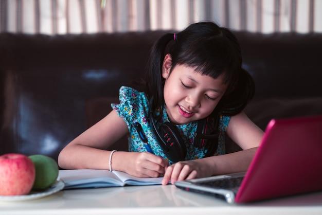 自宅でオンラインレッスン、検疫、オンライン教育の概念の間に社会的な距離を勉強しているかわいいアジアの小さな子供女の子