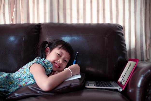 Счастливая девушка маленького ребенка лежа на софе с учить африканским учителем на компьтер-книжке и писать книгу дома, социальное расстояние во время карантина, концепция образования онлайн