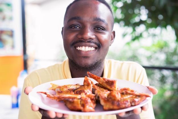 Африканский человек поднимает жареную курицу на блюдо с улыбкой и счастливым