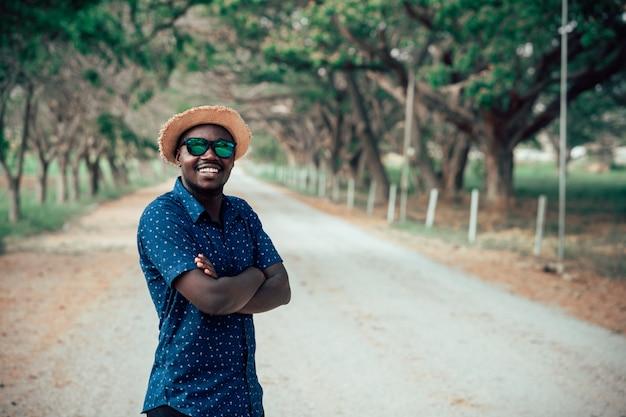 Портрет счастливого африканского человека в солнечных очках, стоя на грунтовой дороге, улыбаясь и глядя