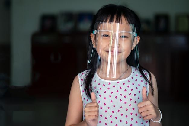 Счастливый маленький ребенок девочка с пластиковой защитной маской для защиты от вирусов на лице