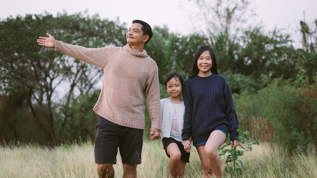Азиатская семья с отцом, матерью и дочерью гуляют в парке с улыбкой и счастьем