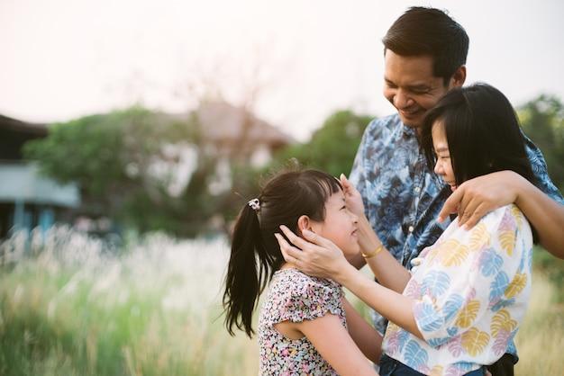 Азиатская семья с отцом, матерью и дочерью улыбаются и счастливы