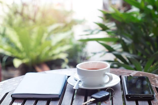 一杯のホットコーヒー、キー、スマートフォン、木製のテーブルの上のノート。