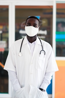 アフリカの医師がフェイスマスクを着用し、聴診器を保持