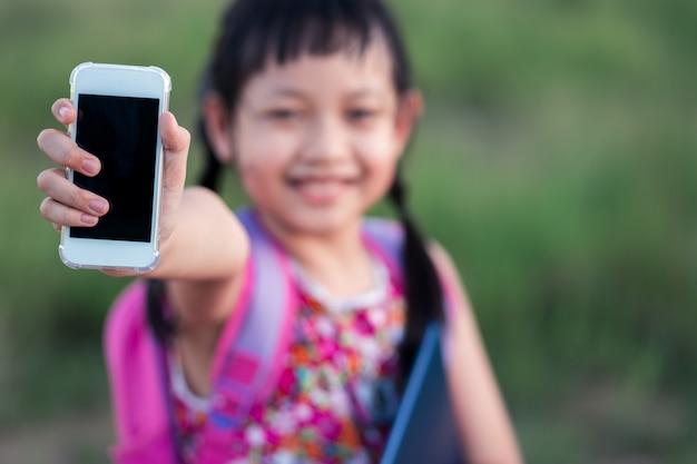 Улыбка маленькая школьница, держа смартфон и книгу с рюкзаком. обратно в школу концепции