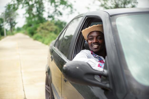 開いているフロントウィンドウが付いている車に座って笑っているアフリカ人ドライバー