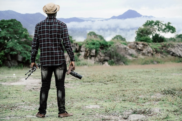 カメラと三脚を保持しているアフリカ人の写真