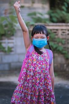学校に行く準備ができているとフェイスマスクを着ているアジアの小さな女の子の学生。