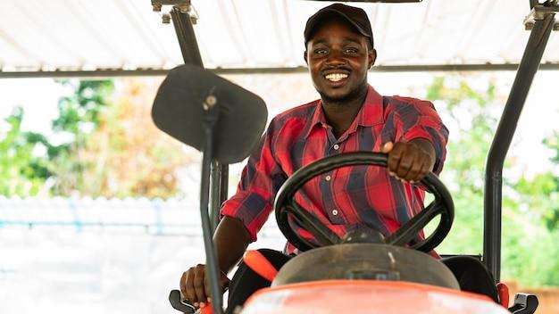 アフリカの農夫がトラクターを運転します。