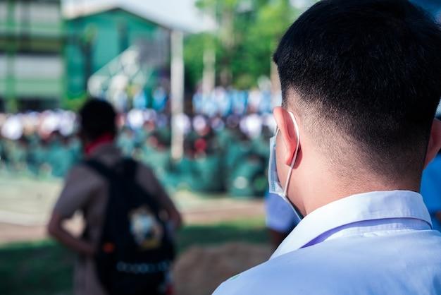 学校に立っている防護マスクの制服の学生